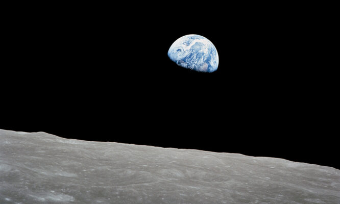 The rising Earth shown about five degrees above the lunar horizon in a telephoto view taken from the Apollo 8 spacecraft (24 Dec 1968)